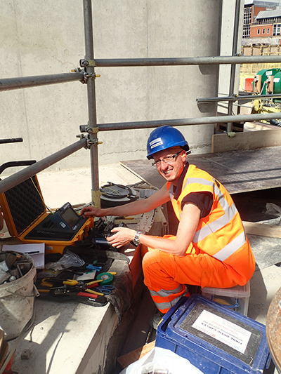Nicky de Battista of University of of Cambridge testing the fiber-optic cable connections at the Principal Tower construction site