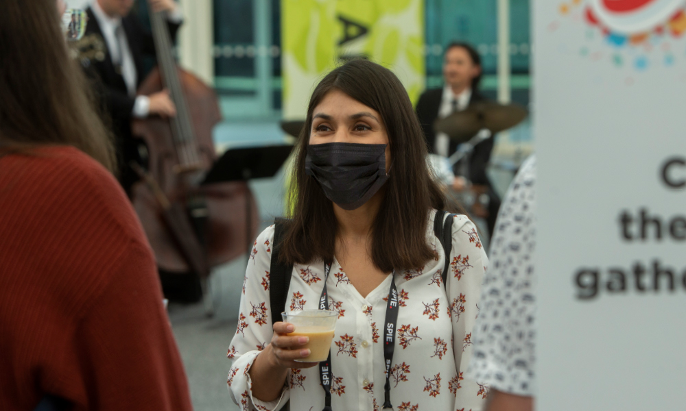 Masked attendee at Optifab networking event
