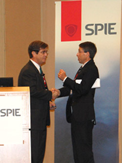 Event chair Steve Eglash, right, welcomes keynote speaker Henry Chesbrough to the podium at the SPIE Photonics Innovation Summit.